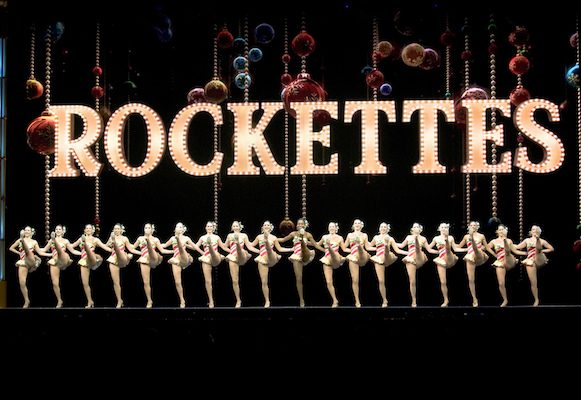 "A headlining feature of the Radio City Christmas Spectacular tour, the Radio City Rockettes perform their trademark high kick-line on stage in the Bryce Jordan Center to a rock-and-roll version of ""The Twelve Days of Christmas."" The Christmas Spectacular's tour performance in University Park included the Rockettes and other performers including Santa Claus, the host of the evening."